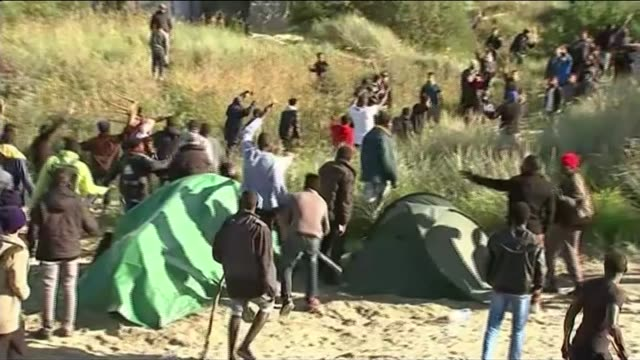 violent clashes between migrants and police ext migrant running along brandishing a saw clashes between different gangs of migrants - calais stock videos & royalty-free footage