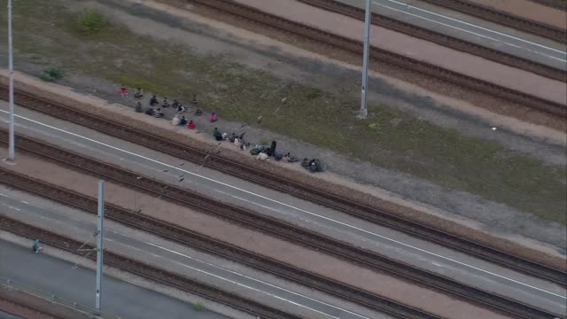 air views of eurotunnel entrance and migrants air view migrants sitting beside tracks - calais stock videos & royalty-free footage
