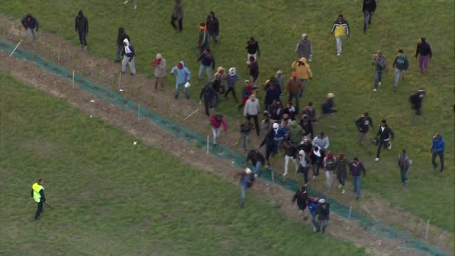 david cameron criticised for 'swarm' comment france calais migrants running across field as police officers try to steer them away - exile stock videos & royalty-free footage