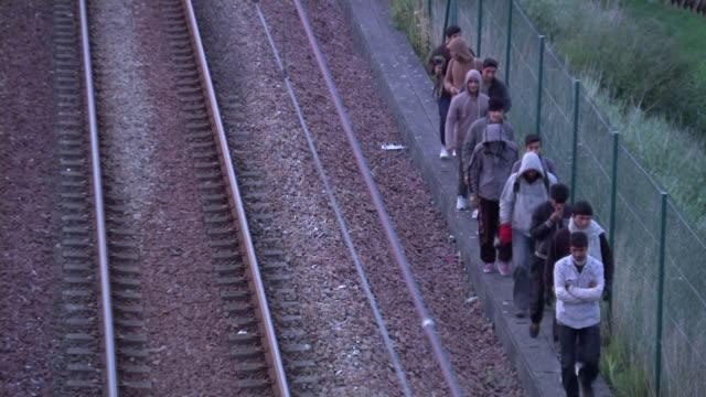 philip hammond criticised for 'maurauding' comment 3072015 / t30071522 line of migrants walk alongside channel tunnel railway track migrants crawling... - calais stock videos and b-roll footage
