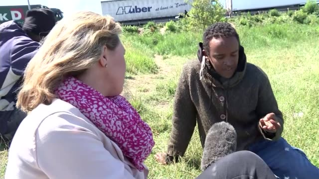 second night of security breaches day wide shot migrants in field next to motorway migrants sitting on grass vox pop to sudan egypt italy i don't... - calais stock videos and b-roll footage