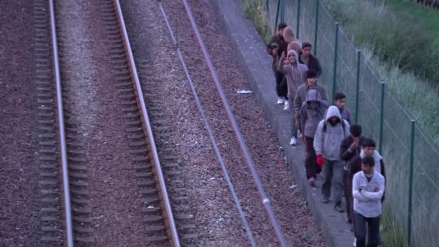 security breaches continue france calais migrants crawling through hole in chainlink fence high angle view migrants along beside railway tracks high... - calais stock videos and b-roll footage