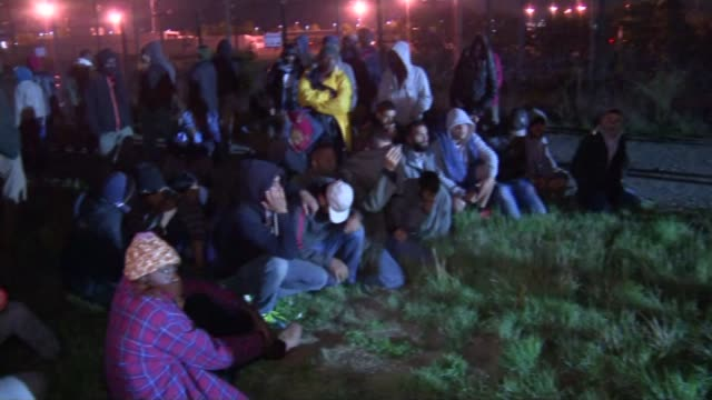 calais migrant crisis: security breaches continue; france: calais: ext / night variuos shots of group of migrants as seated on ground alongside... - 移民点の映像素材/bロール