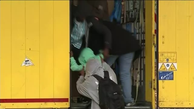 strike ends but migrant problem continues group of migrants clamber into back of lorry young boy mustafa lifted into back of lorry with them lorry... - calais stock videos & royalty-free footage