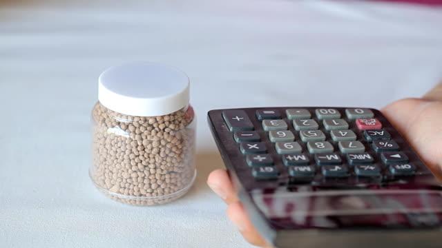 vídeos y material grabado en eventos de stock de calculadora y fertilizante gránulos en botella de plástico - potasio