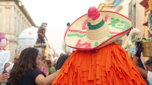 calendas is a parade and celebration typical from oaxaca, mexico. woman dressed in a orange costume and a sombrero on foreground - sombrero stock videos & royalty-free footage