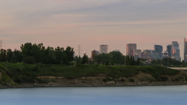 Calgary Glenmore Skyline Timelapse with a rapid pan-right mid shot starting at the parkland and revealing the dense urban skyline