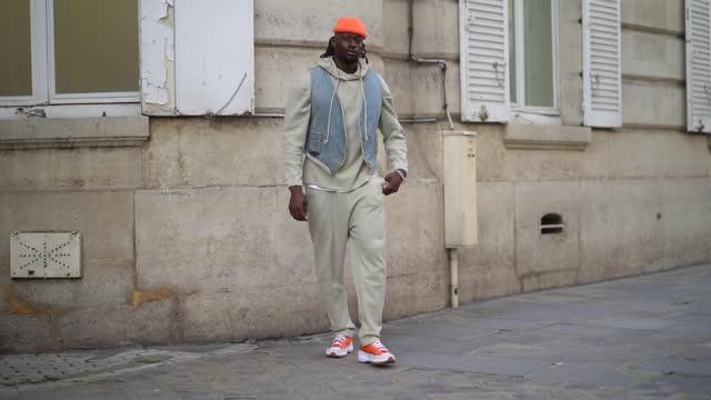 vidéos et rushes de cali chiki wears a neon orange beanie hat, a beige hoodie sweater, a sleeveless blue denim jacket, beige sport jogger pants, neon orange sneakers... - pantalon
