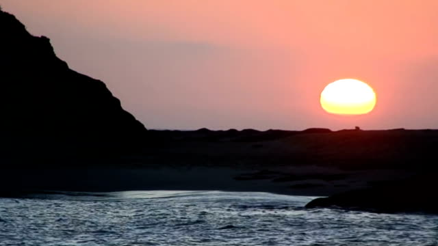 California beach sunset with a rocky silhouette