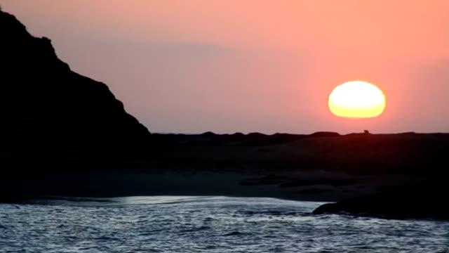 カリフォルニアのビーチの夕日で、ロッキーシルエット