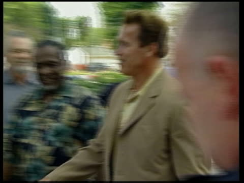 California Arnold Schwarzenegger campaigning as along and shakes hands with children MS Schwarzenegger shaking children's hands MS Schwarzenegger...