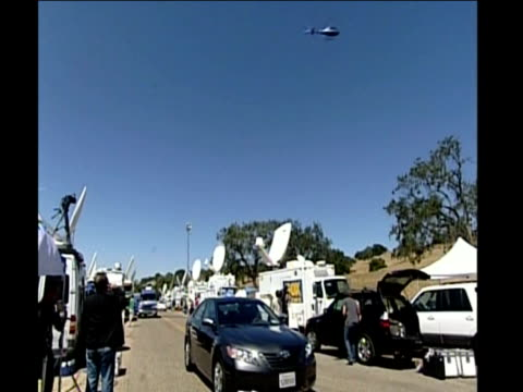 media and television crews outside neverland ranch, fans posing in front of gates bedecked with floral wreaths and police car on patrol - ネバーランドバレーランチ点の映像素材/bロール