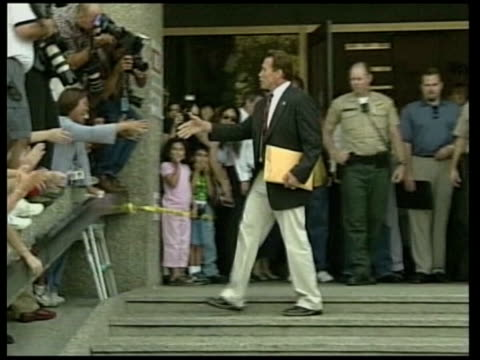 california: ext side arnold schwarzenegger along to register to become next governor of california as asks woman behind desk if she knows who he is... - arnold schwarzenegger stock videos & royalty-free footage