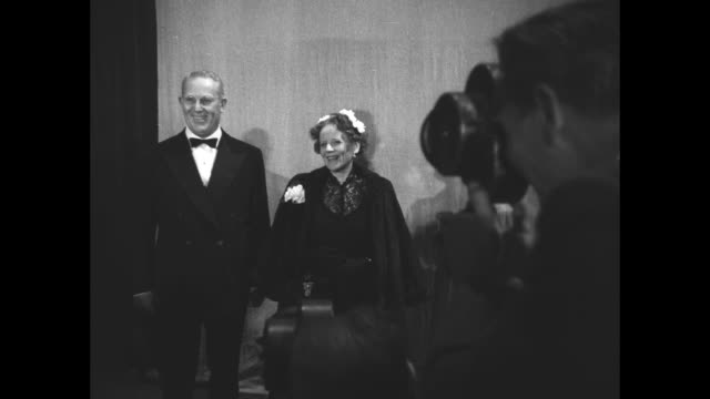 vidéos et rushes de california governor earl warren poses for photos with his wife, nina warren, inside the shrine auditorium in los angeles, where they are attending... - shrine auditorium