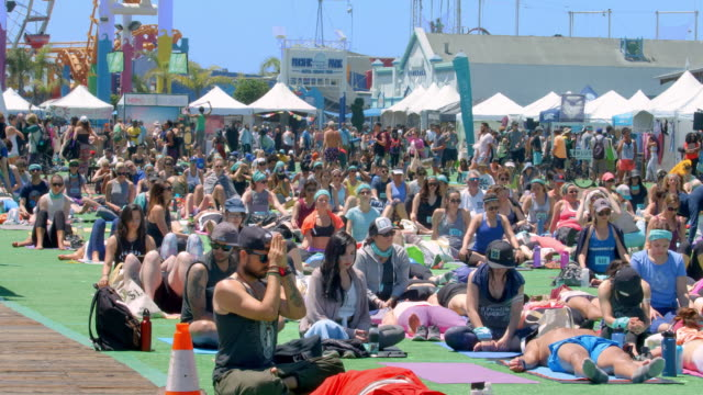 vídeos de stock e filmes b-roll de california healthy lifestyle, crowd of people practicing yoga fitness class on santa monica pier in los angeles, california, 4k, from raw file - santa monica