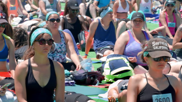 california healthy lifestyle, crowd of people practicing yoga fitness class on santa monica pier in los angeles, california, 4k, from raw file - sun visor stock videos & royalty-free footage