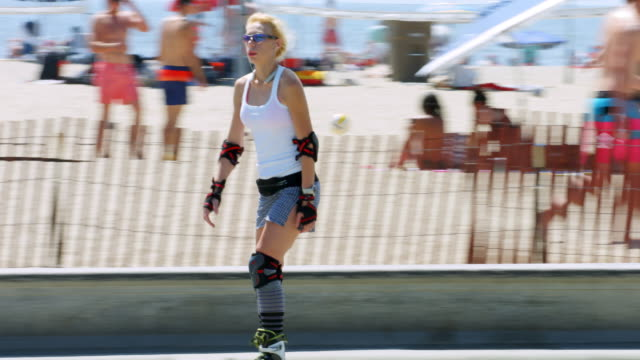 vidéos et rushes de california healthy lifestyle, people roller skating, walking and riding bicycles on santa monica beach in los angeles, california, 4k, from raw file - plan en travelling