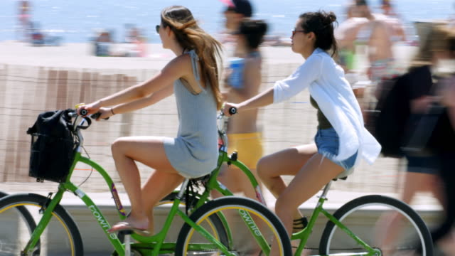 California healthy lifestyle, people walking and riding bicycles on Santa Monica Beach in Los Angeles, California, 4K, from RAW file