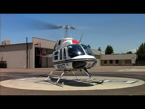 vidéos et rushes de california highway patrol helicopter lifting off from helipad / tilt up to upward view of helicopter hovering in air / fresno, california - fresno