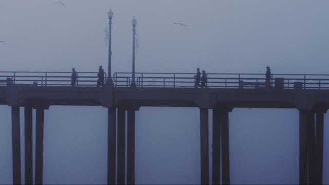 usa, california, huntington beach, people on pier over sea at dusk - huntington beach california stock videos and b-roll footage