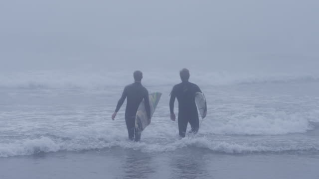 vidéos et rushes de usa, california, huntington beach, two surfers looking at waves - amitié masculine