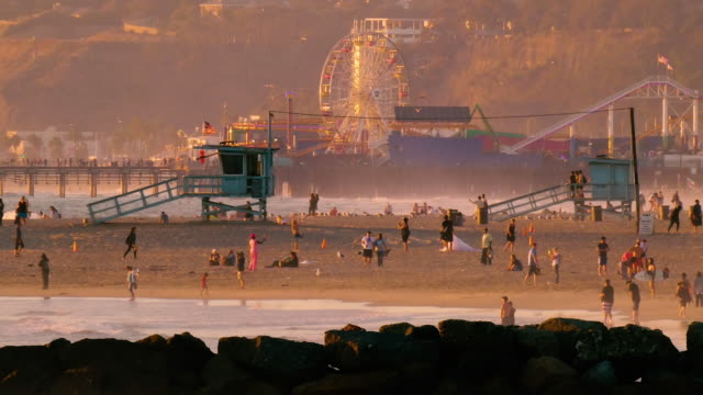 california idyllic beach scene looking towards santa monica pier on a beautiful summer day - cabina del guardaspiaggia video stock e b–roll
