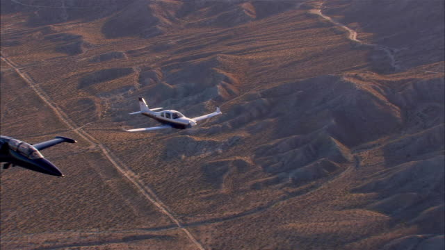 stockvideo's en b-roll-footage met air to air, usa, california, mojave desert, aero l-39 albatross and lancair legacy flying over mountains - luchtmacht