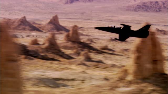 ms, ts, usa, california, mojave desert, aero l-39 albatross flying low above rocks in desert - united states airforce stock-videos und b-roll-filmmaterial
