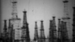 1938: California oil drilling fields steel derrick tower rigging.