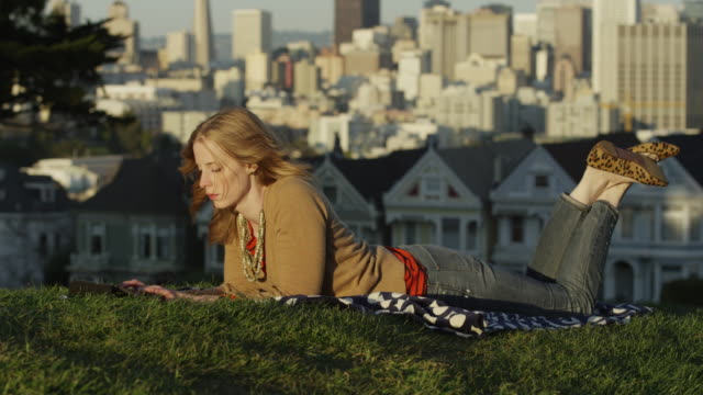 usa, california, san francisco, alamo square park, woman lying on grass and using a digital tablet - auf dem bauch liegen stock-videos und b-roll-filmmaterial
