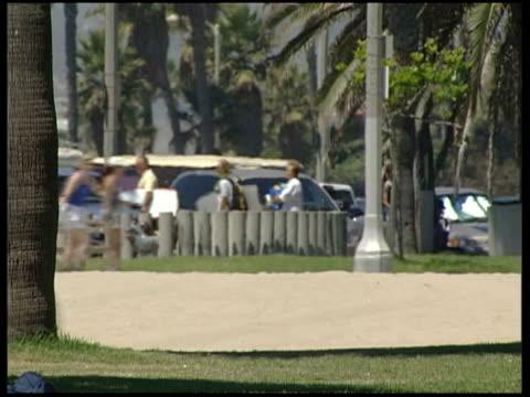 santa barbara beach / los angeles; person pushing belongings along / people cycling and walking along / woman wearing bikini roller skating along /... - 女子ボクシング点の映像素材/bロール