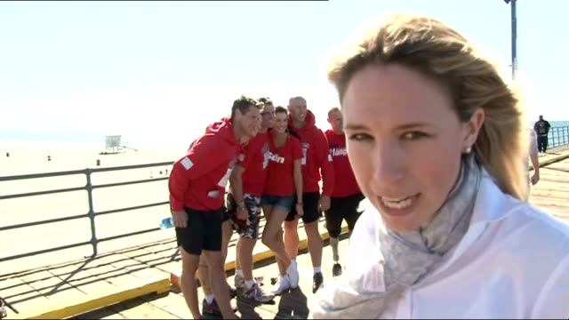 Santa Monica Reporter to camera Unidentified Royal Marine runner interview SOT US Flag flying from flagpole Group of peopel standing on beach as...