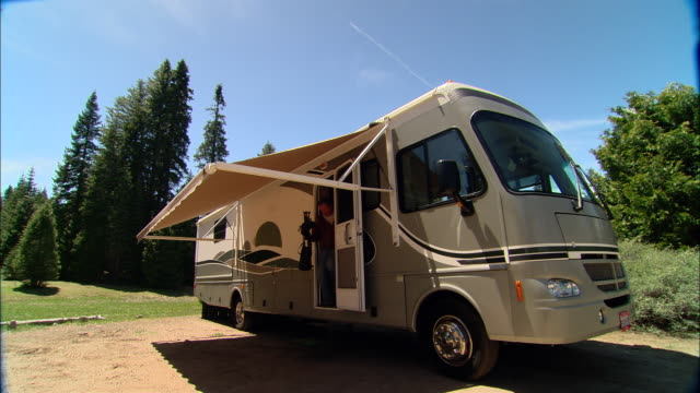 vídeos y material grabado en eventos de stock de ms, pan, usa, california, shaver lake, couple at  motor home with awning - silla plegable