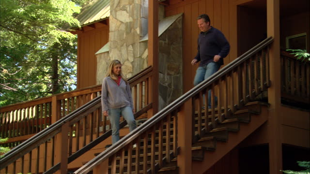 MS, PAN, TU, USA, California, Shaver Lake, Couple descending bungalow wooden steps
