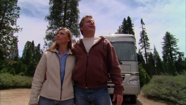 MS, PAN, USA, California, Shaver Lake, Couple looking around beside motor home
