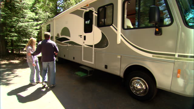 ms, usa, california, shaver lake, couple looking at motor home - gemeinsam gehen stock-videos und b-roll-filmmaterial