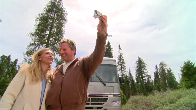 MS, PAN, USA, California, Shaver Lake, Couple photographing self and hugging beside motor home