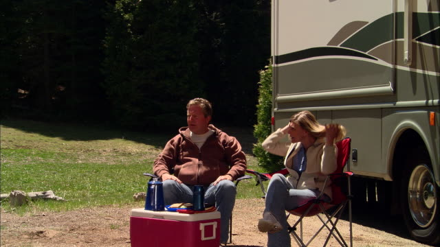 vídeos y material grabado en eventos de stock de cu, zo, ms, usa, california, shaver lake, couple relaxing beside motor home with awning - silla plegable