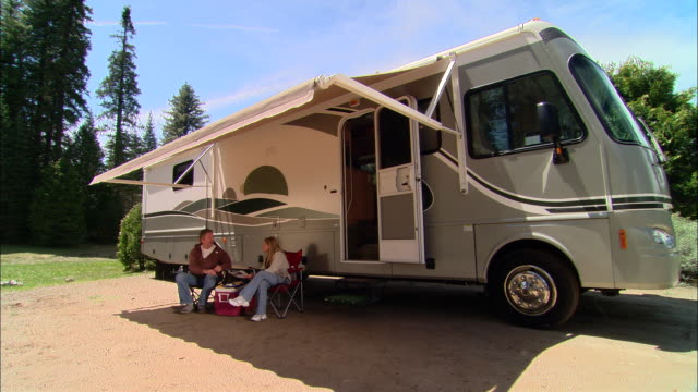 ms, pan, usa, california, shaver lake, couple relaxing beside motor home with awning - camper van stock videos and b-roll footage