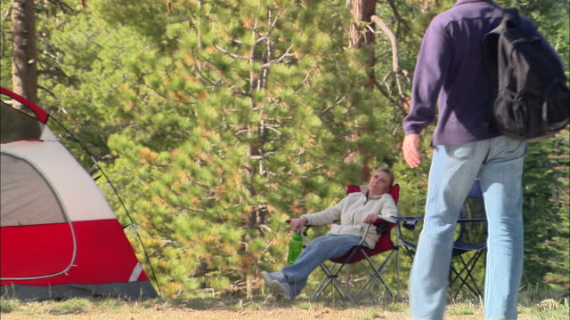 vídeos de stock e filmes b-roll de ms, usa, california, shaver lake, couple relaxing in forest - encostado