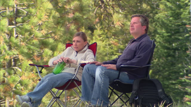 vídeos y material grabado en eventos de stock de cu, usa, california, shaver lake, couple relaxing in forest - silla plegable