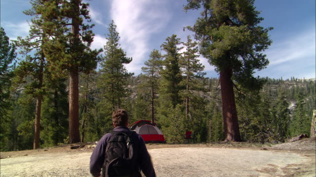 MS, TD, USA, California, Shaver Lake, Couple walking down hill towards dome tent, rear view