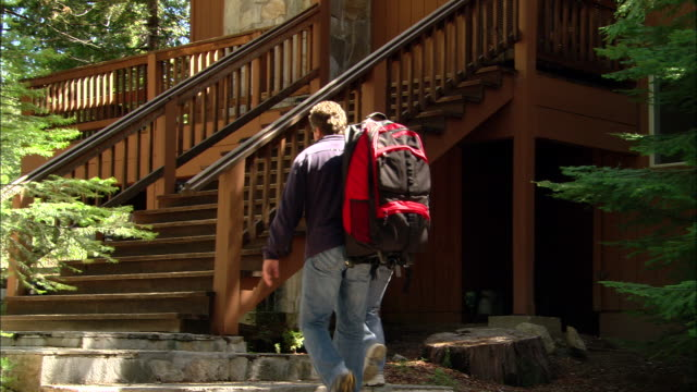 MS, PAN, USA, California, Shaver Lake, Couple with backpacks ascending bungalow steps, rear view