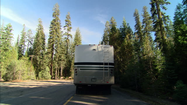 ms, usa, california, shaver lake, motor home traveling through forest, rear view - camper van stock videos & royalty-free footage