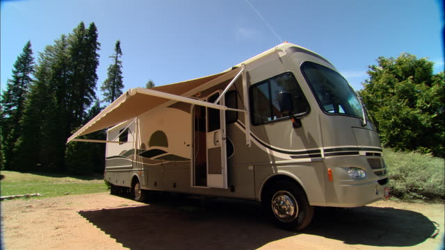 ms, pan, usa, california, shaver lake, motor home with awning parked on parking at forest - camper van stock videos & royalty-free footage