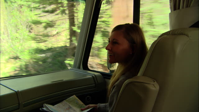 cu, usa, california, shaver lake, woman holding map sitting in front seat of motor home - 40 44 jahre stock-videos und b-roll-filmmaterial