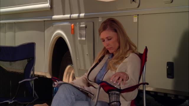 vídeos de stock, filmes e b-roll de cu, usa, california, shaver lake, woman relaxing beside motor home - cadeira dobrável