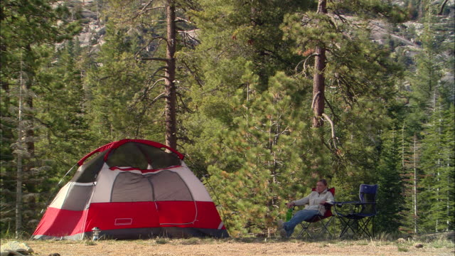 vídeos y material grabado en eventos de stock de ms, usa, california, shaver lake, woman relaxing in forest beside dome tent - recostarse