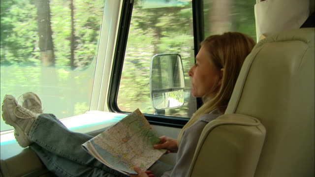 cu, usa, california, shaver lake, woman with map on laps sitting in front seat of motor home - 40 44 jahre stock-videos und b-roll-filmmaterial