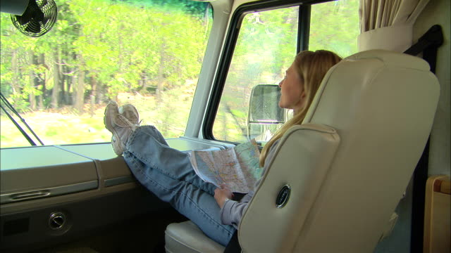 vídeos y material grabado en eventos de stock de cu, usa, california, shaver lake, woman with map on laps sitting in front seat of motor home - recostarse
